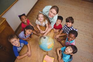 Cute pupils smiling around a globe in classroom with teacher at the elementary school.jpeg