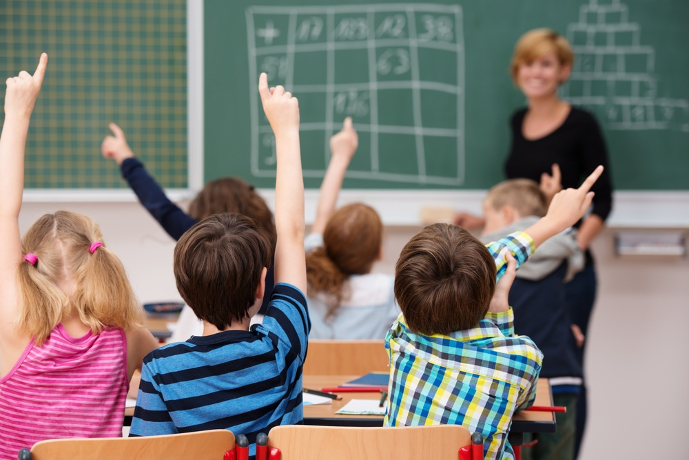 Intelligent group of young school children all raising their hands in the air to answer a question posed by the female teacher, view from behind-1