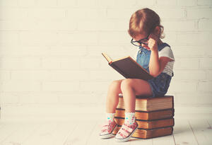 child on stack of books