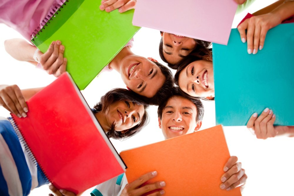 Happy group of students holding notebooks - isolated over white-1.jpeg